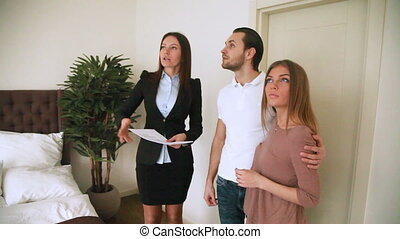 Female real estate agent meeting young couple, showing...
