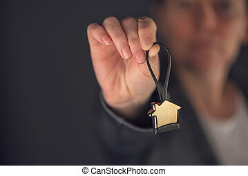Female real estate agent with house model key ring