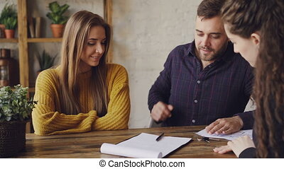 Female realtor is reading purchase and sell agreement to young couple, man is signing document and taking key, shaking hands with agent and kissing his wife.