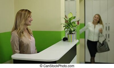 Female receptionist meeting client in beauty salon - Smiling...