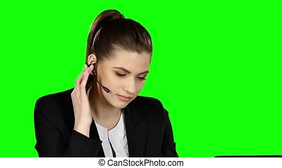 Female receptionist working on computer and talking on the telephone in call center. Green screen