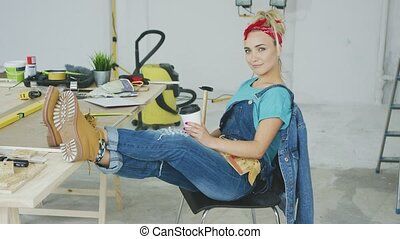 Female relaxing at carpenter workbench with drink - Young...