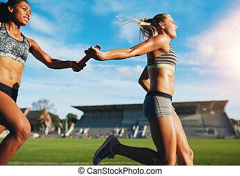 Female relay team passing the baton - Female athletes...