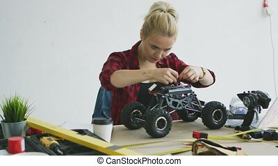 Female repairing radio-controlled car - Beautiful young...