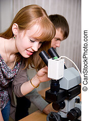 Female researcher looking through a microscope