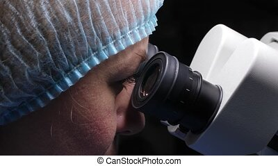 Female researcher looking through microscope - Close-up of ...