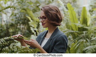 A female researcher standing in botanical garden, exploring plants.