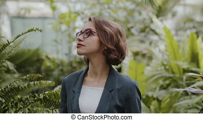 Female researcher standing in botanical garden, exploring ...