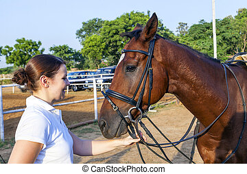 female rider hugging with her horse