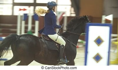 Female rider on the horse jumping over the hurdle at show...