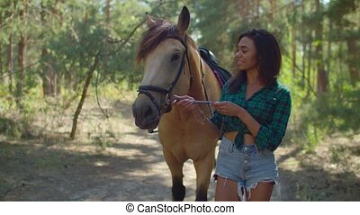 Female rider with purebred horse strolling in wood - Outdoor...