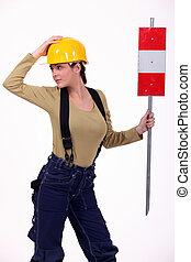 Female road-worker with sign
