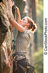 Female rock climber climbing a stone structure