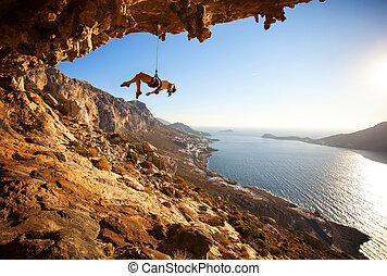 Female rock climber hanging on rope on cliff - Female rock...