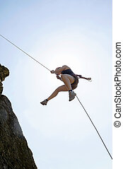 Female Rock Climber Rappelling