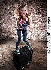 Female rocker - Young punk rocker on a speaker in front of a...