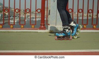 Female roller feet riding backwards on city bridge -...