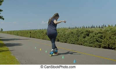 Rear view of active woman inline skating backwards crisscross through cones standing in line on park alley. Skillful female practicing slalom backward bypass cones riding rollerblades in public park.