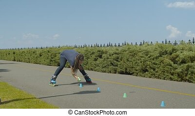 Active woman in roller blades picking up cones standing in line on park walkway while rollerskating over them legs apart. Young female roller with afro-braids finished inline skating practice in park.