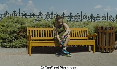 Attractive woman roller sitting on bench and putting roller skates on feet before riding in well-kept public park. Active female with ponytail from afro-braids going to rollerblading outdoors.