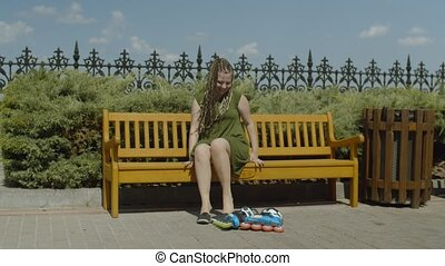 Female roller putting on shoes sitting on bench - Young...