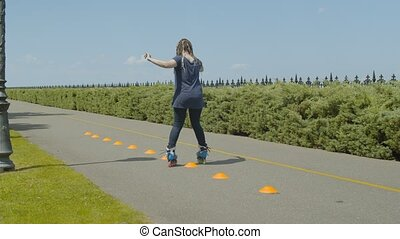 Rear view of skillful woman rollerblading inline roller skates past cones on park footpath. Active female with ponytail from afro-braids training skill of crisscross ride during inline slalom outdoor.