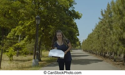 Active young woman rollerblading at speed with pizza box working in fast pizza delivery service in public park. Positive female riding rollerblades along park alley hurry deliver pizza to customer.
