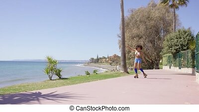 Female rollerskating on the sidewalk - Female wearing blue...