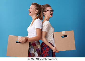 female roommates with a cardboard boxes standing back to back