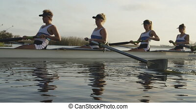 Female rowing team training on a river
