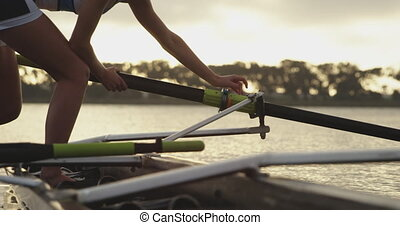Female rowing team training on a river - Side view of a ...