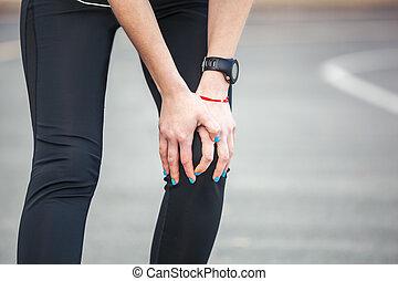 Female runner is holding her injured leg.