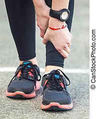 Female runner is holding her injured leg. - Young female...