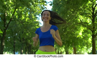 Female runner jogging during outdoor workout in park.