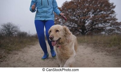 Female runner jogging with her pet for cross race - Low...