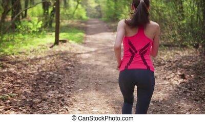 Female runner run in spring sunny forest, slow motion