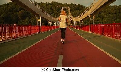 female runner runs on the bridge