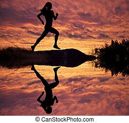 Female runner silhouette against the sunset
