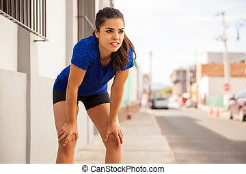 Beautiful young brunette leaning on her knees and taking a break after a long run