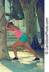 Female runner warming up before jogging.