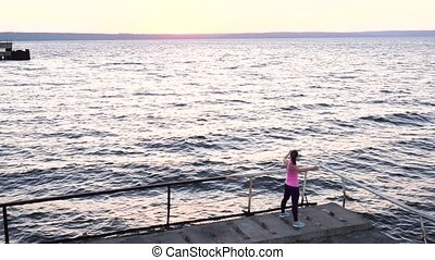 Female Runner Warming Up Outdoors on the Beach