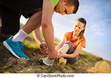 Injury - sports woman with twisted sprained getting help from man touching her ankle.