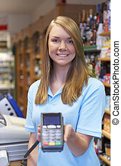 Female Sales Assistant Holding Credit Card Machine