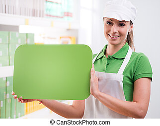 Female sales clerk with green sign