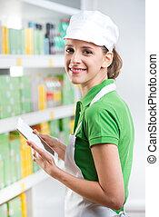 Female sales clerk with tablet at supermarket
