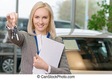 Female sales representative is upholding the car keys. -...
