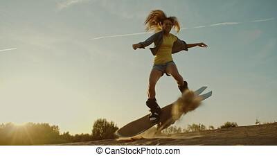 Female sandboarder jumping in desert - Tourists Sand Skiing...