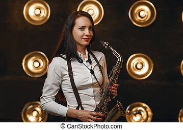 Female saxophonist plays the saxophone on stage - Female ...