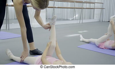 Female school coach keeps foot in correct position of girl...