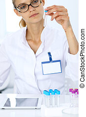 Female scientific researcher in laboratory studying substances or blood sample. Medicine and science concept